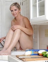 Hot cougar gets on top of the kitchen counter and showers her shaved pussy with the dish sprayer