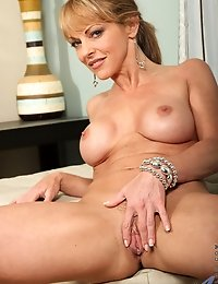 Adorable milf Shayla Laveaux spreads her legs exposing her pussy and her pink clitoris on the sofa