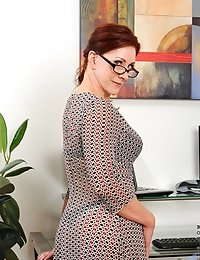 Captivating redhead milf peels off her sheer dress exposing her sexy bra and thong in the office