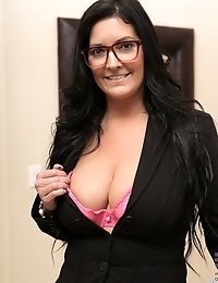 Hot cougar in glasses shows off her abundant cleavage in a sexy bra