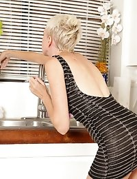 Naughty housewife wears a skin tight dress in the kitchen